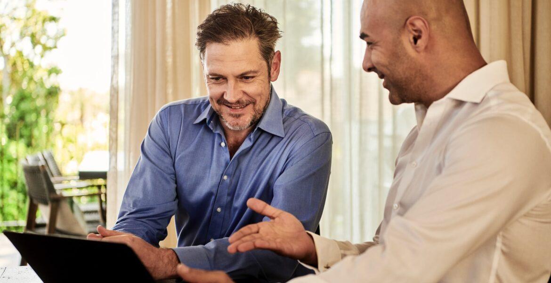 man in blue dress shirt beside man in white dress shirt