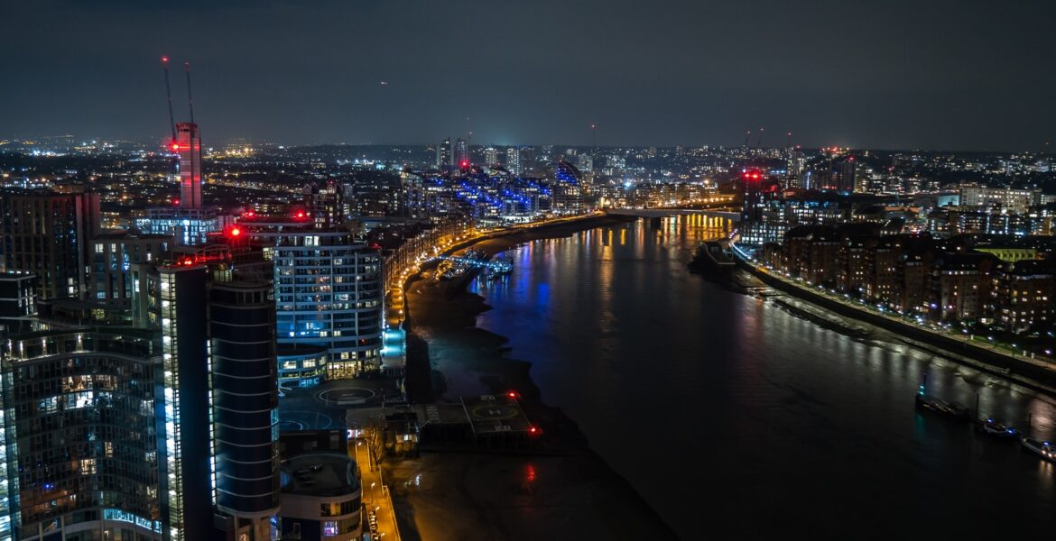 aerial photography city buildings with river during nighttime